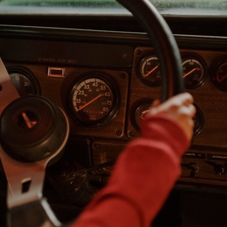 Person in a red sweater steering a car